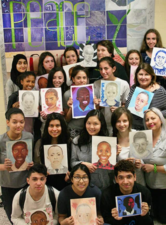 Harrison High School students show off their artwork for kids in Tanzania.