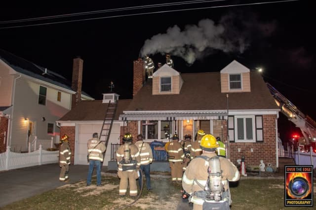 Members of the Mineola Fire Department douse a chimney fire.
