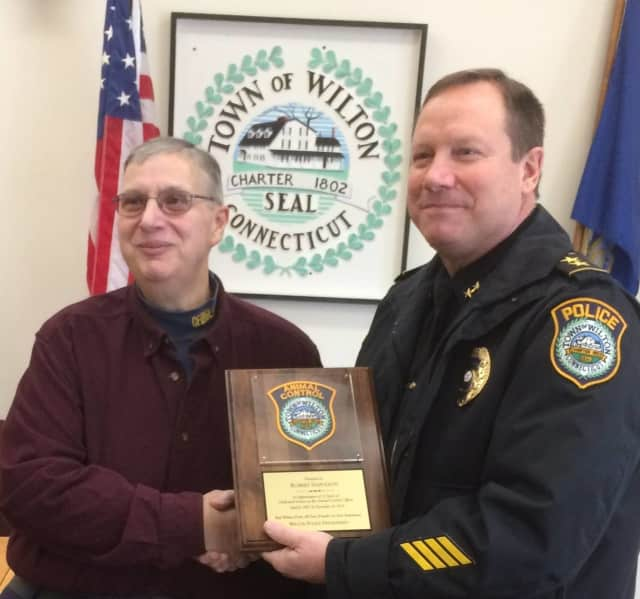 Wilton Police Chief Robert Crosby presents a plaque to Animal Control Officer Robert Napoleon who has retired after 33 years with the Town of Wilton.