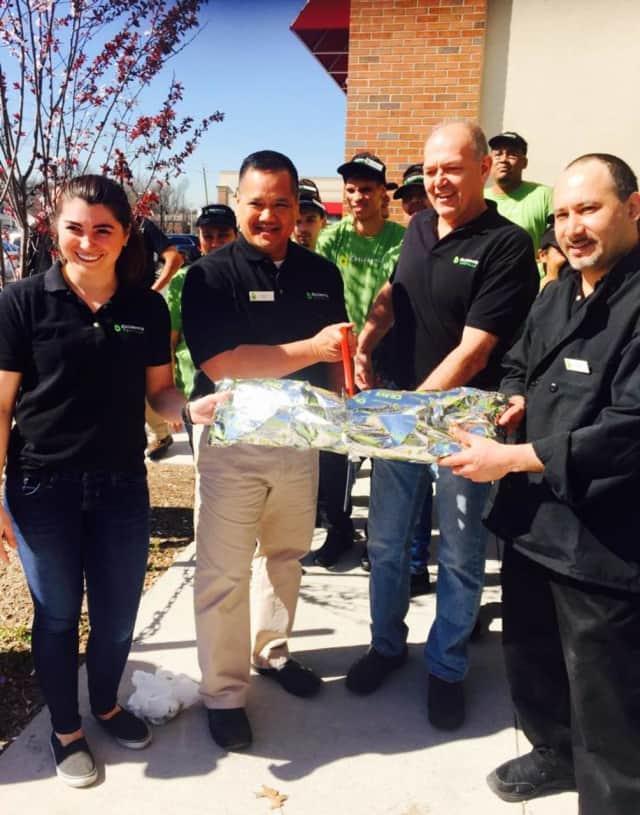 Paul Sanford cuts the ceremonial burrito at California Tortilla's new River Edge location.