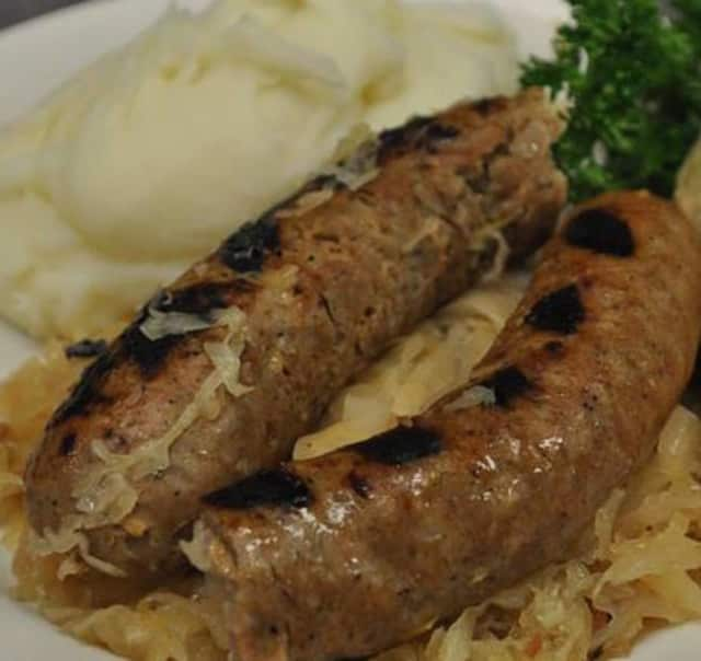 A kielbasa with kapusta dinner with mashed potatoes.