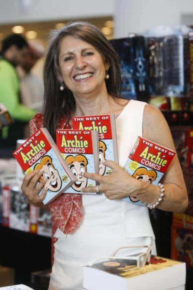 Nancy Silberkleit, publisher and co-CEO of Archie Comics, poses next to a sign proclaiming some of her comic book mottos.