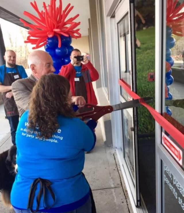 Westport First Selectman Jim Marpe — with his dog, Olivia — uses the giant scissors for the grand opening of a new Petco on the Post Road East.