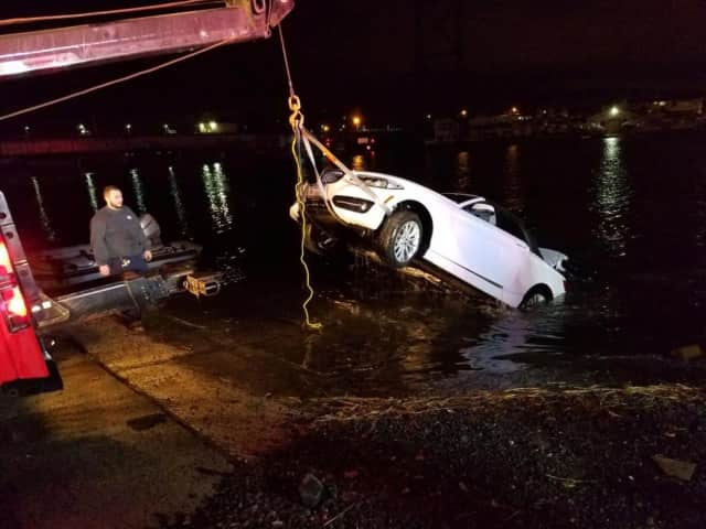 The car is pulled from the Saugatuck River early Sunday in Westport. An elderly man died after the car went into the chilly waters Saturday evening, but first responders saved a woman.