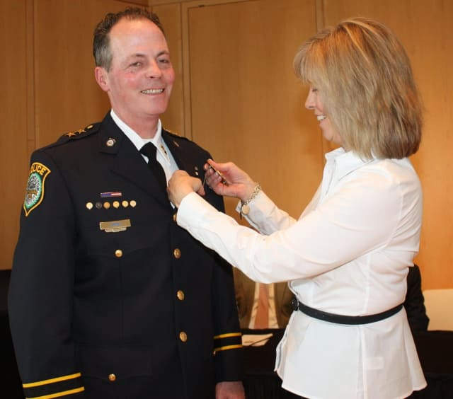 New Wilton Police Chief John Lynch is presented with his new badge by his wife, Ann.