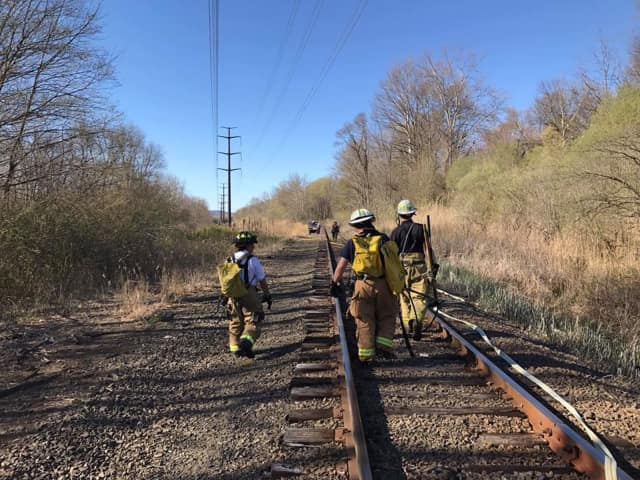 The brush fire is reported along the train tracks in Brookfield on Tuesday.
