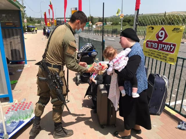 An IDF soldier assists those affected by the mass casualty incident on the Jewish holiday of Lag B'Omer at Mt. Meron, in which 45 people were killed.