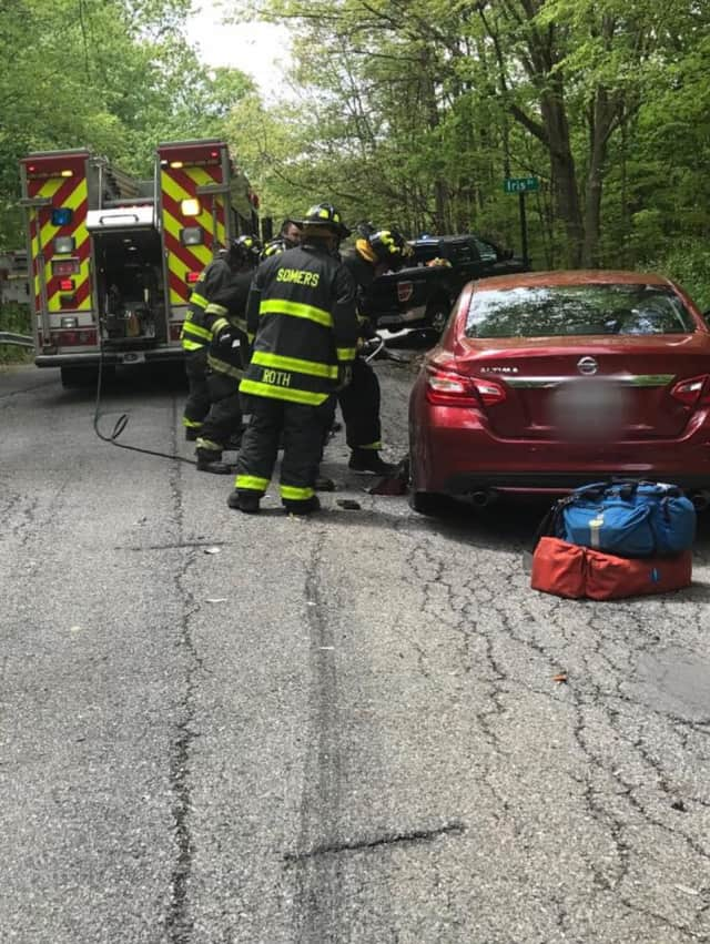 Somer's firefighters work to remove a victim following a car crash.
