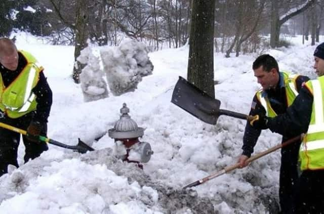 A team of Ridgewood firefighters free a hydrant in this file photo.