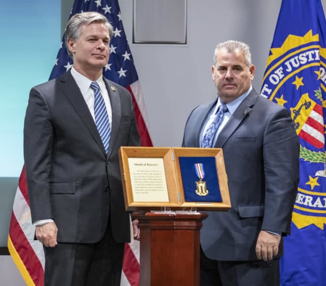 FBI Director Christopher Wray, left, presents Shield of Bravery to Detective Terence Malone