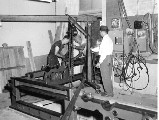 Two men hoist a roll of paper onto a printing press at The Ramsey Journal, part of an exhibit of local history at the Mahwah Museum, opening this month.