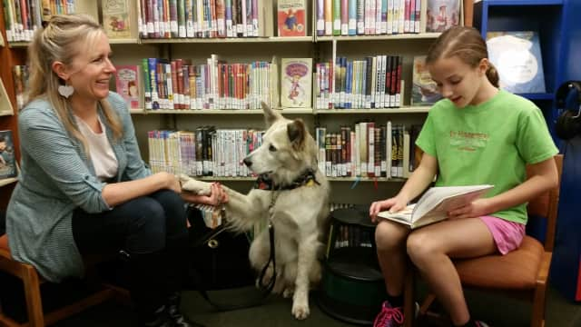 Catherine, a trainer, sits with Ben the dog and Kristina, a patron at Franklin Lakes Public library during the December PAWS event.