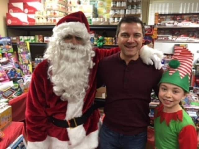 Anthony Mehran with Santa and an elf at the Huffman Koos toy drive event.