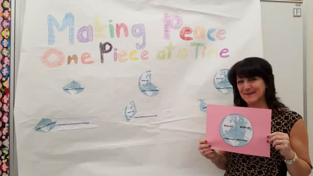"Esther Fletcher with a poster her students made for the ""Peace By Piece"" project."