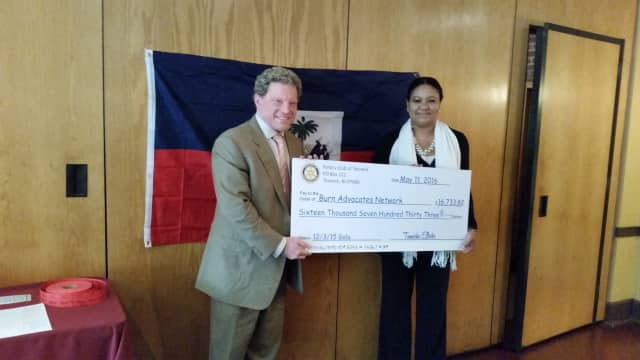 Rotary President Tamarha Ellerbe presents Sam Davis, founder of Haiti's Burn Advocates Network, with nearly $17,000.
