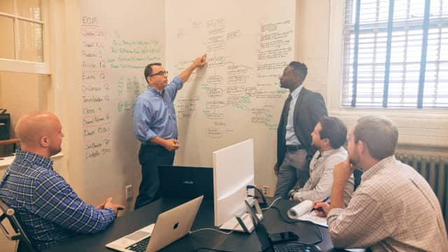 The HelpGrowUSA team works on business solutions at its Clarence Street headquarters in Bridgeport.