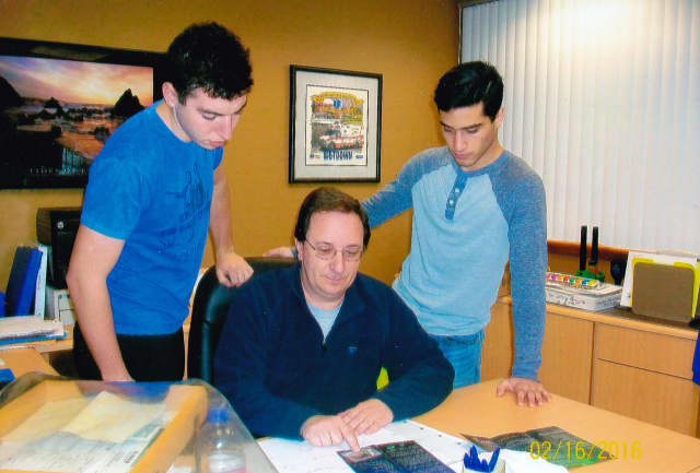 Recycling Coordinator Ron Lottermann reviewing his presentation on the Litter Marshal Program for the League of Women Voters sponsored public program at the high school on March 10. Lavan Naveh is on the left with Idan Michael on the right.
