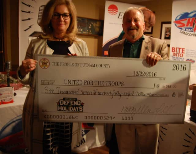 Putnam County Executive MaryEllen Odell presents United For The Troops co-founder Jim Rathschmidt a check from the donations collected through the Defend the Holidays campaign.