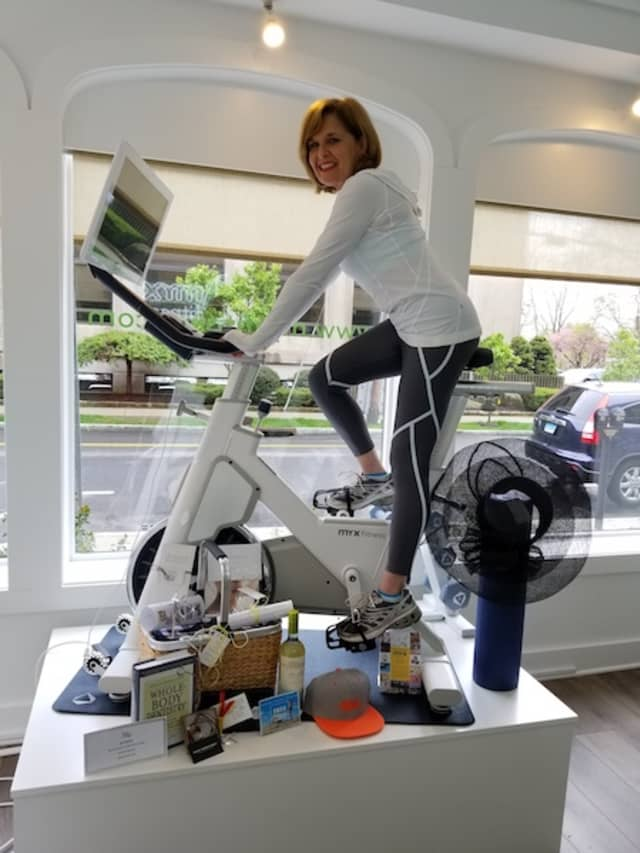 "Deb Lomma of The Winged Tree showcasing the Myx Home Fitness Studio along with the additional products and services included in ""A Curated Myx Basket,"" valued at $2,500. Courtesy Myx Fitness."