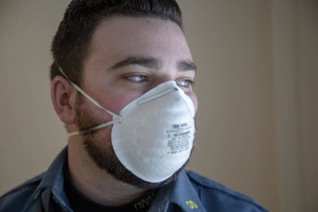 Holy Name Medical Center security guard Brendan McLaughlin dons his face mask.