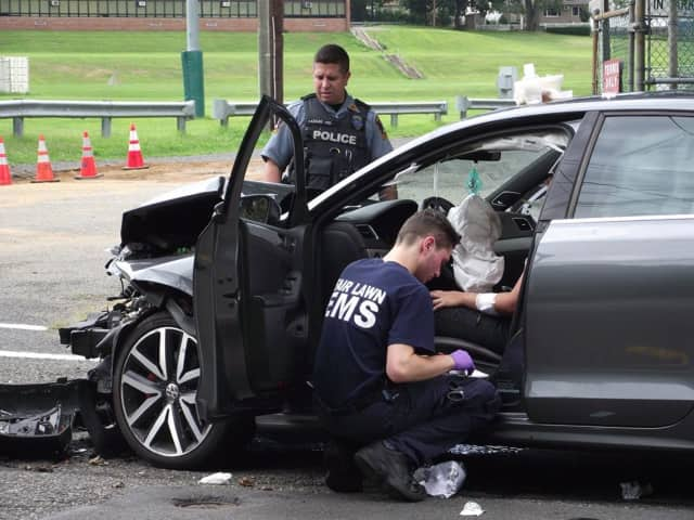 A Fair Lawn police officers surveys the damage to a vehicle involved in a Saturday crash, as EMS tends to the victim.