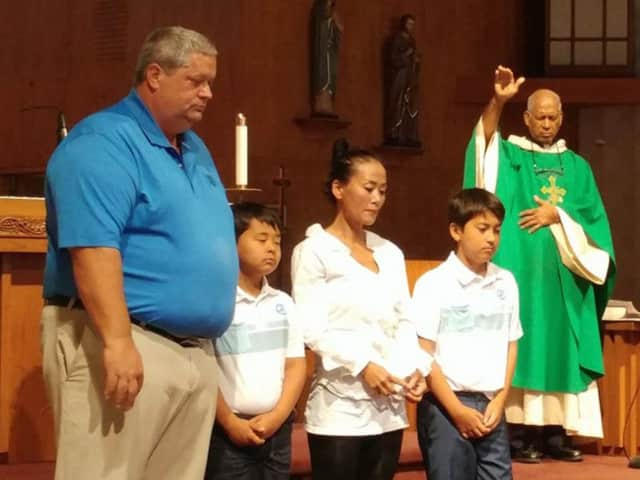 Richard and Jung Courville, with their children, receive a blessing at St. Jerome in Norwalk.