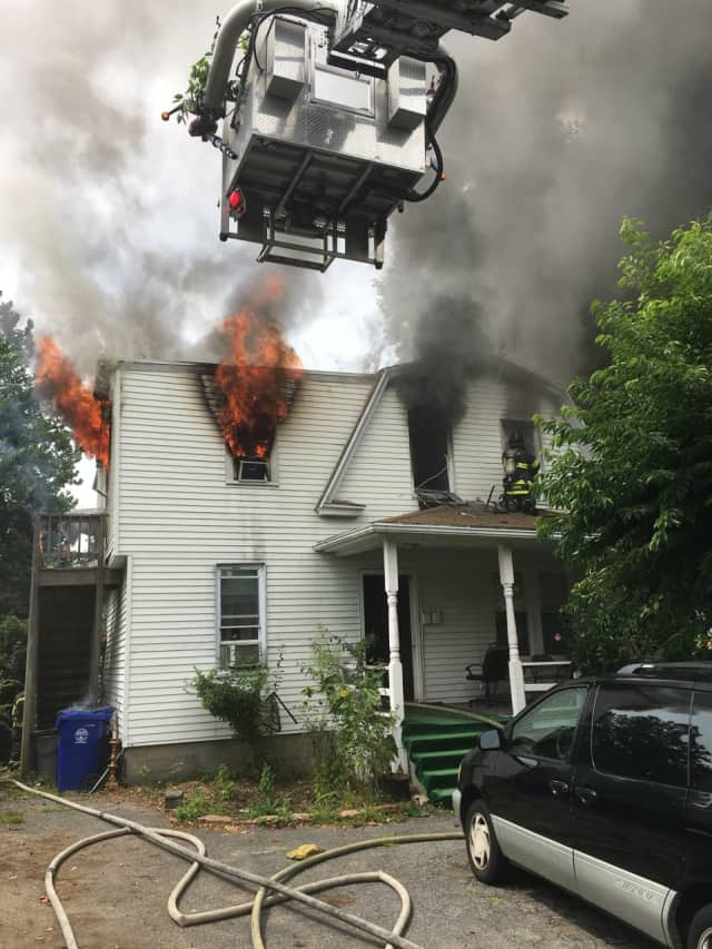 Smoke and fire pour from a home at 67 Fair St. as the Norwalk Fire Department goes to work to extinguish the blaze Saturday.