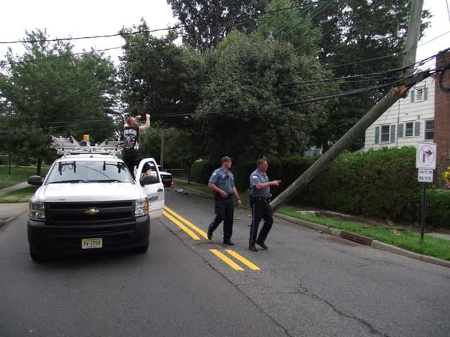 Ridgewood police assess the damage done to a utility pole after an SUV crashed into it on Tuesday.