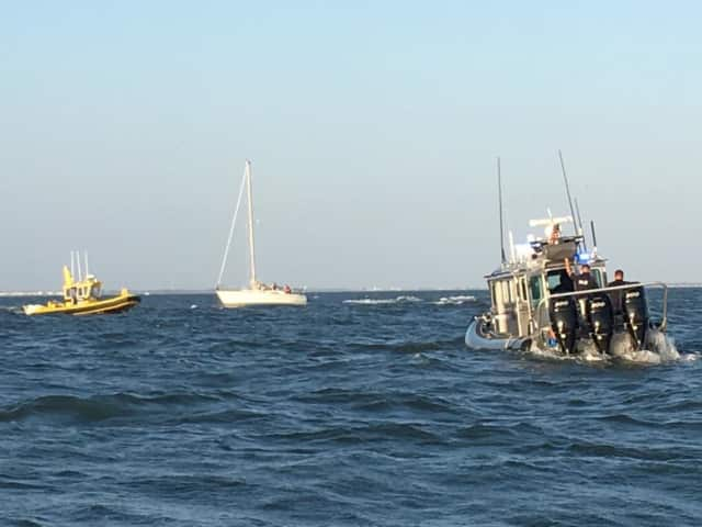 Marine officers battle 3-foot waves as they help a sailboat that ran aground with six people aboard.