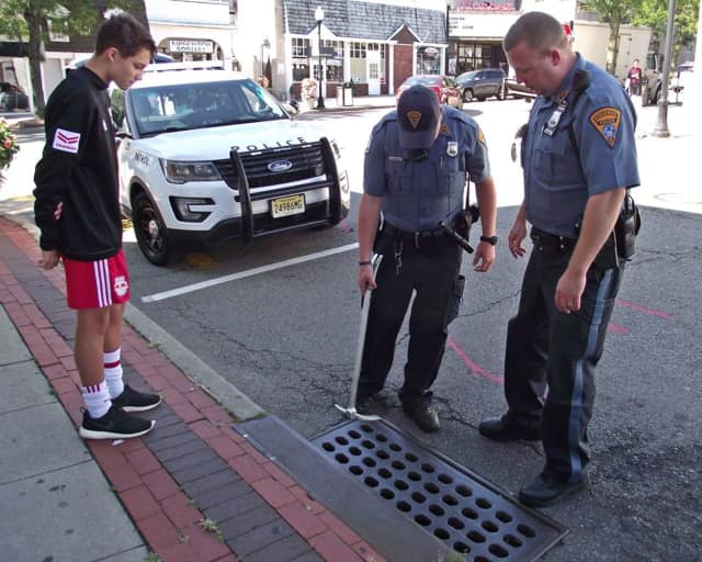 Police rescue a cell phone from a storm drain in Ridgewood.