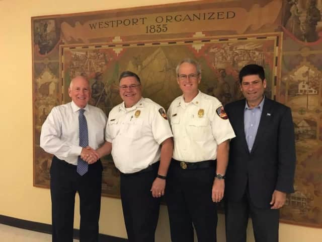 Deputy Fire Chief Robert Kepchar is congratulated by First Selectman Jim Marpe, Selectman Avi Kaner, and Fire Chief Robert Yost.
