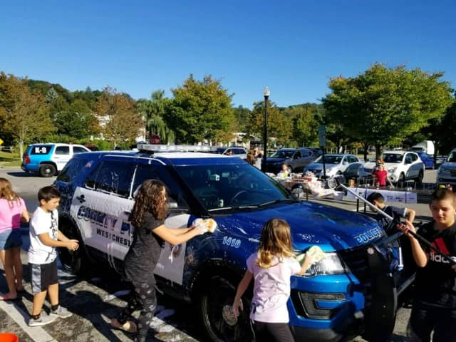 Students from Mount Kisco Elementary School wash local police cars during a school fundraiser.