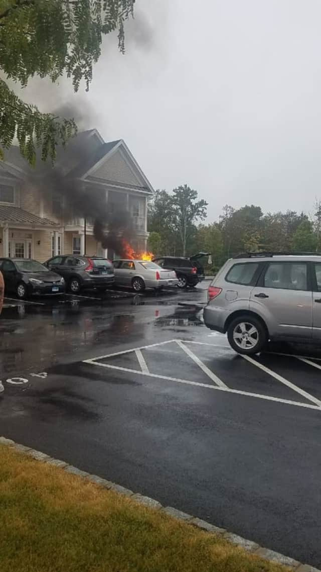 "A car is fully on fire Sunday morning at at the Rivington ""The Mews"" complex in Danbury."