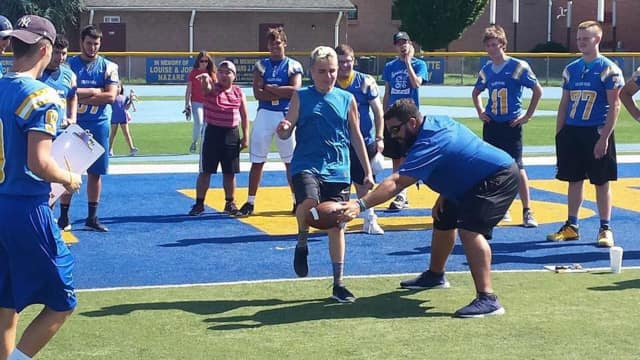 The Special Angels get tips from the LHS players on how to punt, pass and kick.