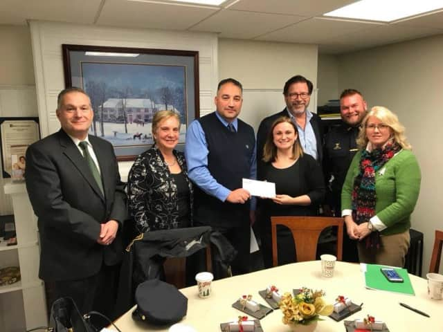 The Trumbull Police Union makes a donation to the Mary J. Sherlach Counseling Center. See story for IDs.