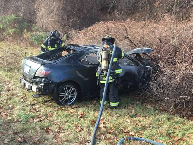 Fairfield firefighters quickly douse a burning car on I-95 on Wednesday afternoon.
