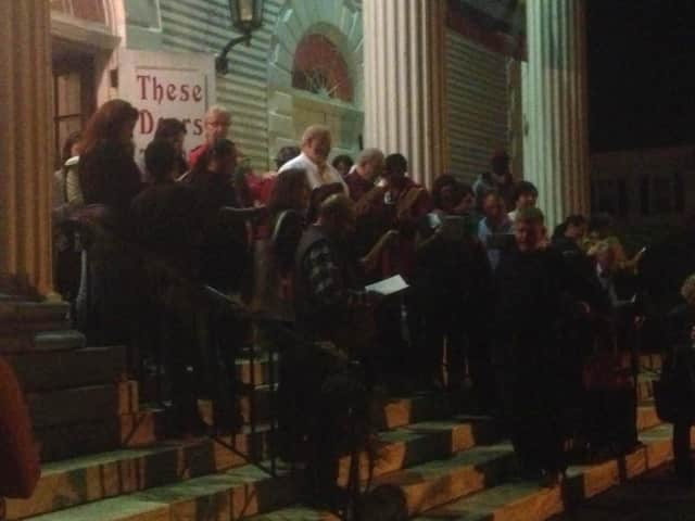 Parishioners gather on the steps of the First Congregational Church in Norwalk to sing Christmas Carols on Thursday evening.