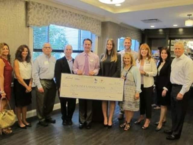 The Armonk, Mount Kisco, Somers, Greenwich and Chappaqua-Millwood Chambers of Commerce present a check for $2.985 to help fight Alzheimer's disease at the Bristal in Armonk