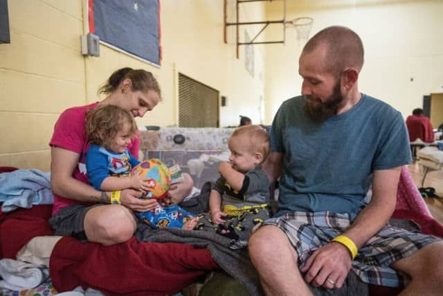 Two parents play with their children, ages 2 and 1, on their cot in a shelter in San Antonio on Sunday as Hurricane Harvey slams Texas.