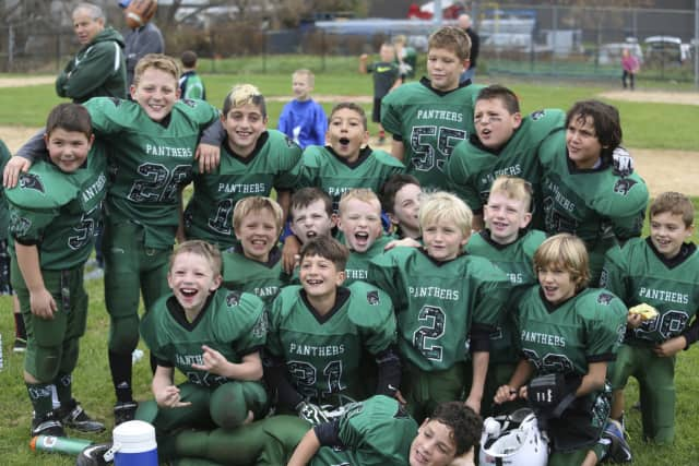 The third- and fourth-grade White team players are all smiles after completing an undefeated season.