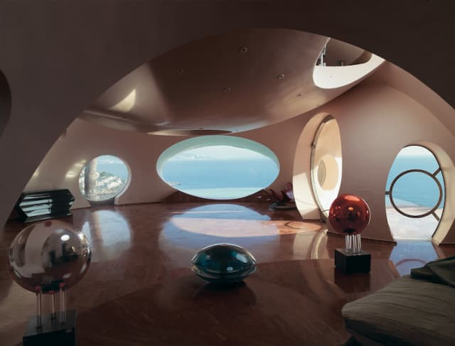 """Antti Lovag, Palais Bulles, 1989. Théoule-sur-Mer, Cannes, France. The infinity-style swimming pool lends a further layer of surreal abstraction to the house. Inside, the collaboration between Antti Lovag and Pierre Cardin resulted in equally unexpected interiors. Photograph by Richard Powers, as featured in """"The Iconic House: Architectural Masterworks Since 1900."""" Courtesy Thames & Hudson."""