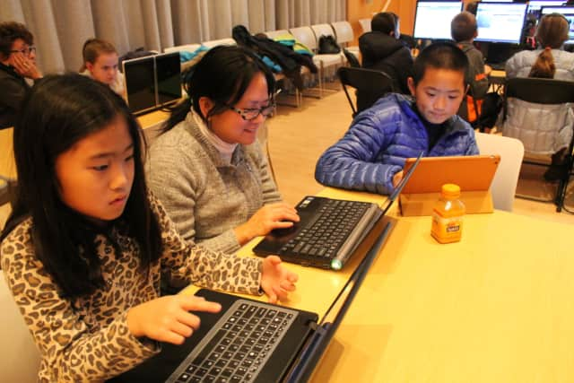 Breaking Code is a family affair for the Kauh family. From left, Sienna, mom Christine, and Evan learn how to code at Wilton Library's Breaking Code event held last year.