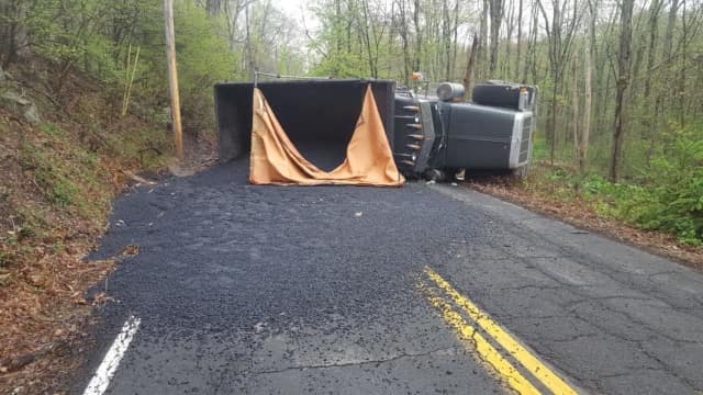 A dump truck turned over in New City, spilling asphalt and closing South Mountain Road.