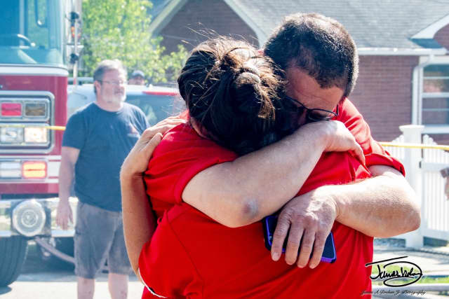 The Cianfaglione family hug each other following a devasting fire destroyed their home and five cats.