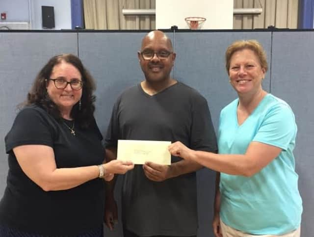 Sgt. Craig Lynch, the program director, accepts a donation for the Bogota Emergency Services Youth Academy  from Bogota Education Association representatives Vicki Shepard and Laura Ketchum.