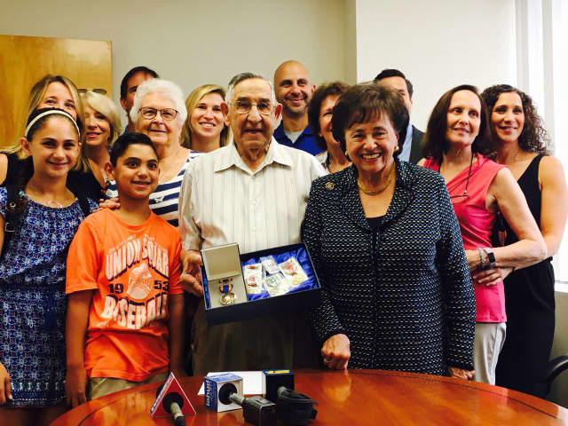 Alfred Magnatta receives his medals from Congresswoman Nita Lowey.