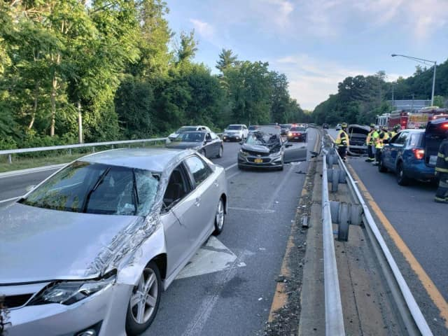 A car went airborne after striking a guardrail on the Saw Mill River Parkway in Dobbs Ferry, landing on two other vehicles.