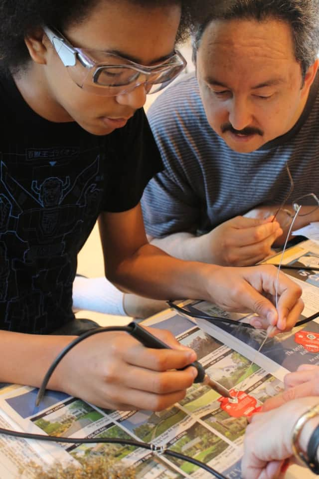 Jonathan Ayala with his dad at last year's Innovation Day learning how to solder at the Wilton Library.