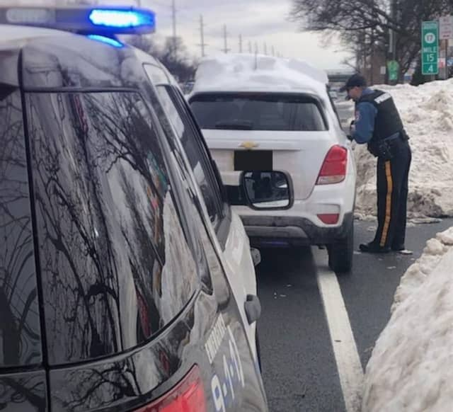 A Paramus police officer pulls over a motorist with rooftop snow Wednesday, Feb. 3, 2021.