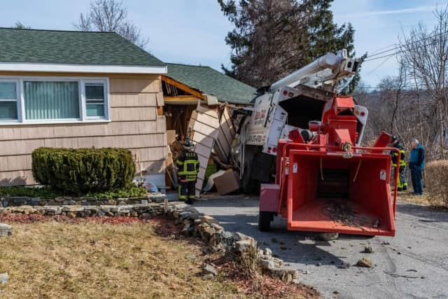 A truck rolled into a house while working on trees in the area.